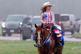 Second-grader Jadyn Thibodeaux rides to school as part of Piney Woods Elementary School's Go Texan Day, Friday, Feb. 23, 2018, in Splendora.