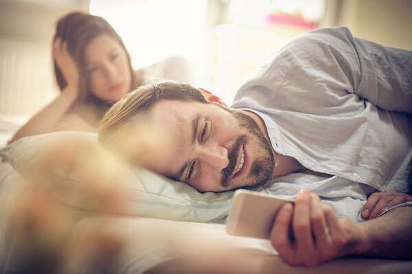 Young couple in bed. Focus on man. Space for copy.
