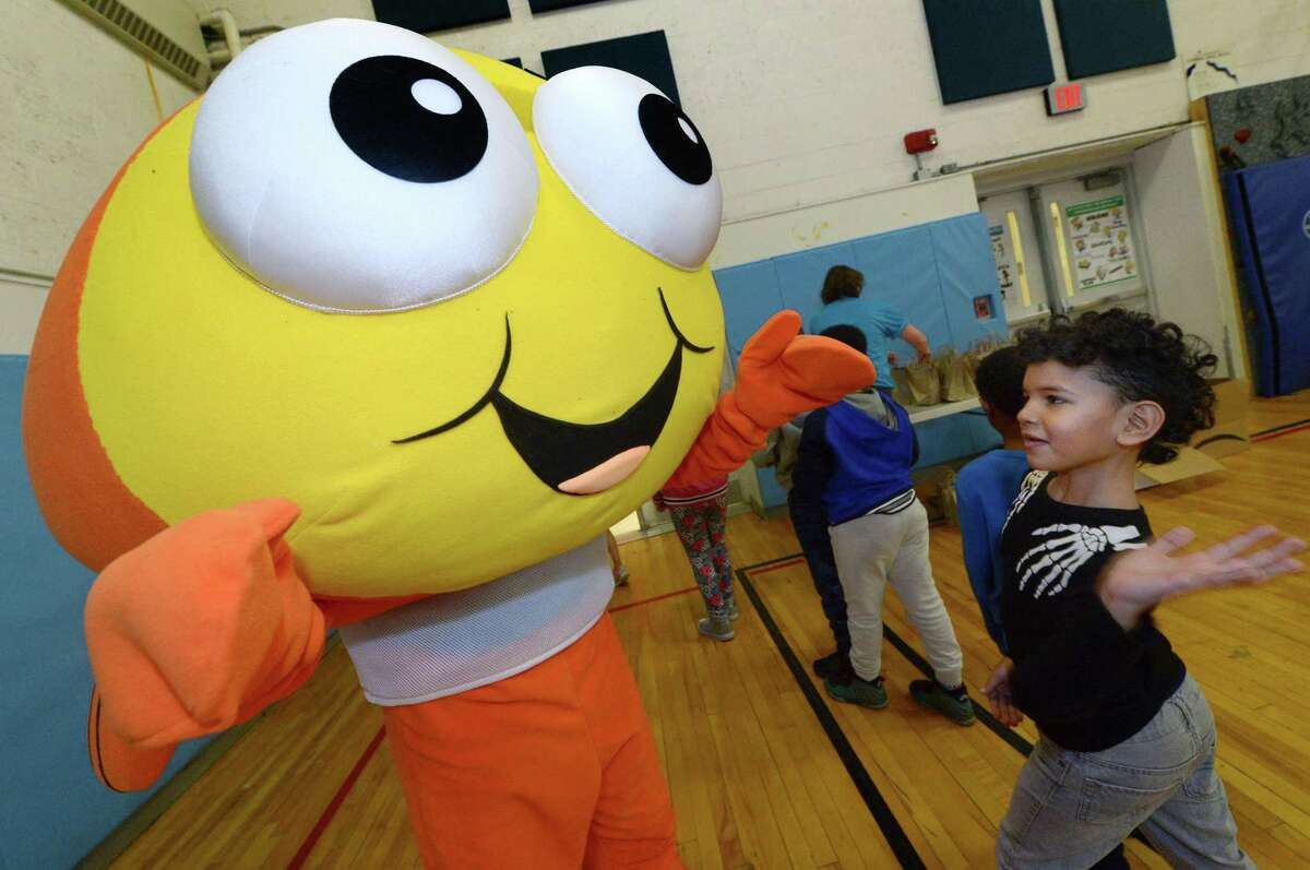 Brookside Elementary School second grader Alex Perez, right, is greeted by Mark Pizzi as he dresses up as the Goldfish mascot, Bubbles, during a presentation by Goldfish, a new business teaching children ages 4 months to 12 years how to swim on Wednesday at Brookside in Norwalk.