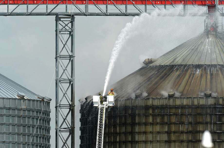"Firefighters spray water on a silo to cool 10,000 tons of smoldering wood pellets at the Port of Port Arthur on Monday. According to city spokeswoman Risa Carpenter, hot spots located by officials Saturday evening ignited early Sunday due to a temperature spike. City firefighters extinguished the flames and began cooling the structure. Port of Port Arthur Director Floyd Gaspard said the fire was started by é'internal combustion.é"" The pellets originated from the German Pellets facility in Woodville, where a fire occurred in April of 2014.  On Feb. 27, a conveyor belt loading a ship at the Port of Port Arthur with several tons of wood pellets caught fire, setting the wood ablaze and sending a colossal cloud of black smoke into the air. Photo taken Monday, April 17, 2017 Guiseppe Barranco/The Enterprise Photo: Guiseppe Barranco, Photo Editor"