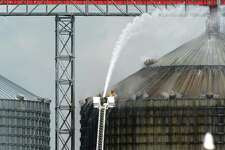 """Firefighters spray water on a silo to cool 10,000 tons of smoldering wood pellets at the Port of Port Arthur on Monday. According to city spokeswoman Risa Carpenter, hot spots located by officials Saturday evening ignited early Sunday due to a temperature spike. City firefighters extinguished the flames and began cooling the structure. Port of Port Arthur Director Floyd Gaspard said the fire was started by é'internal combustion.é"""" The pellets originated from the German Pellets facility in Woodville, where a fire occurred in April of 2014.  On Feb. 27, a conveyor belt loading a ship at the Port of Port Arthur with several tons of wood pellets caught fire, setting the wood ablaze and sending a colossal cloud of black smoke into the air. Photo taken Monday, April 17, 2017 Guiseppe Barranco/The Enterprise"""