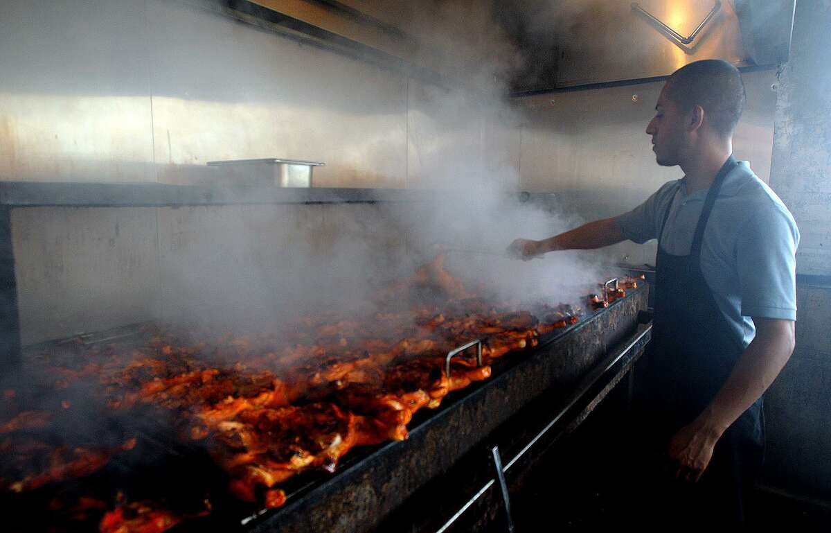 Pollos Asados Los Nortenos employee Azael Rodriguez cooks chickens over a mesquite fired grill in2013.