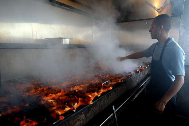 "Pollos Asados Los Norteños employee Azael Rodriguez cooks chickens over a mesquite fired grill in 2013. Restaurant owner Frank Garcia worked at many restaurants in San Antonio before starting his own four years ago. Garcia said if you want to find his restaurant, ""just follow the smoke."""