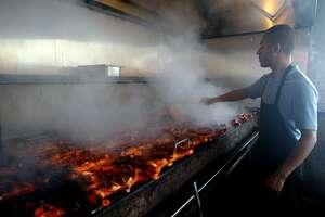"""Pollos Asados Los Norteños employee Azael Rodriguez cooks chickens over a mesquite fired grill in 2013. Restaurant owner Frank Garcia worked at many restaurants in San Antonio before starting his own four years ago. Garcia said if you want to find his restaurant, """"just follow the smoke."""""""