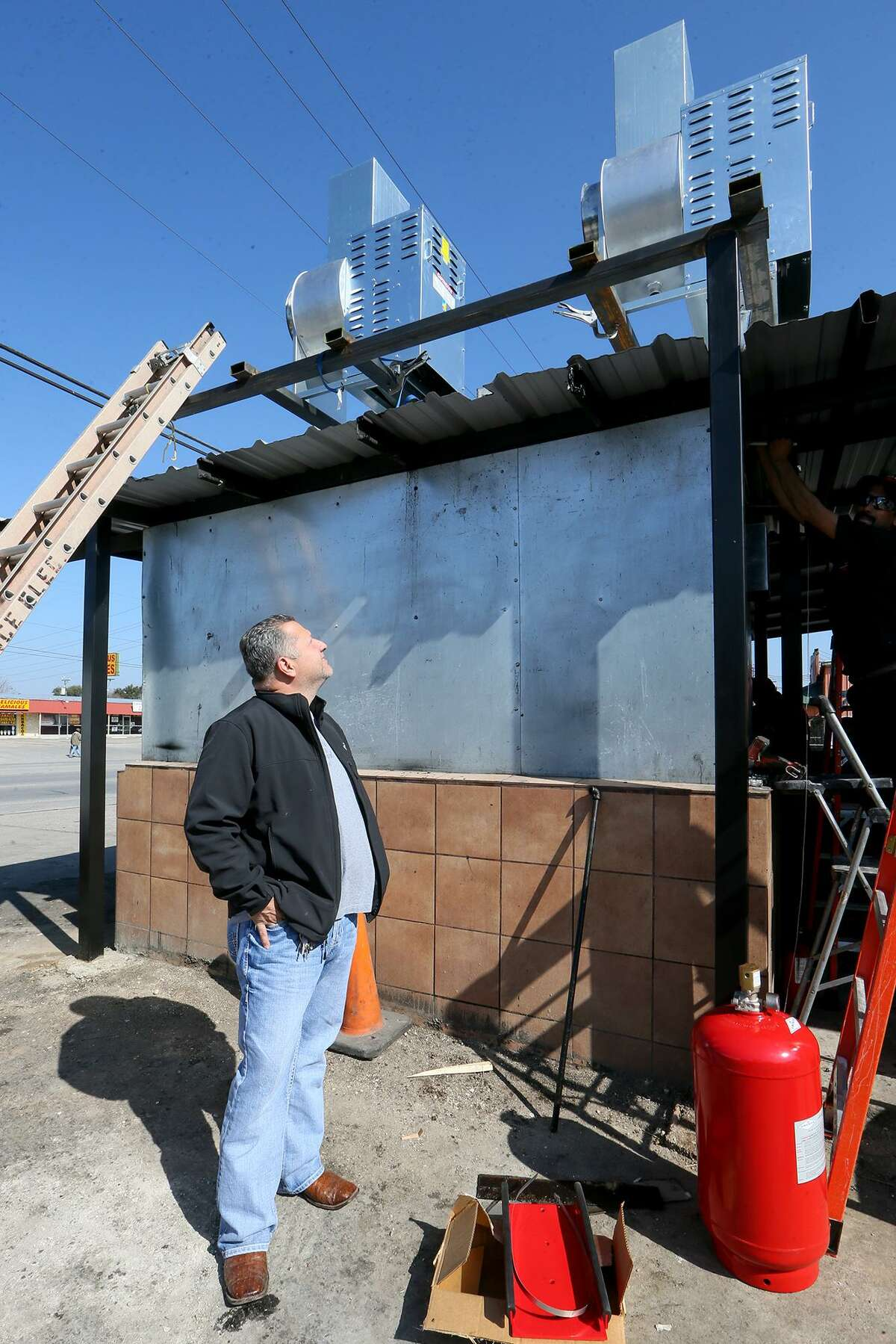 Owner Fank Garcia inspects two high velocity exhaust fans installed on the smokehouse at Pollos Asados Los Norteños in Feb. 2016. Garcia installed new fire suppression and exhaust systems, but it wasn't enough to keep government officials from shutting down the restaurant.