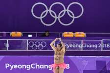 A shirtless man clad in a tutu dances on the rink following the men's 1,000m speed skating event medal ceremony during the Pyeongchang 2018 Winter Olympic Games at the Gangneung Oval in Gangneung on February 23, 2018.