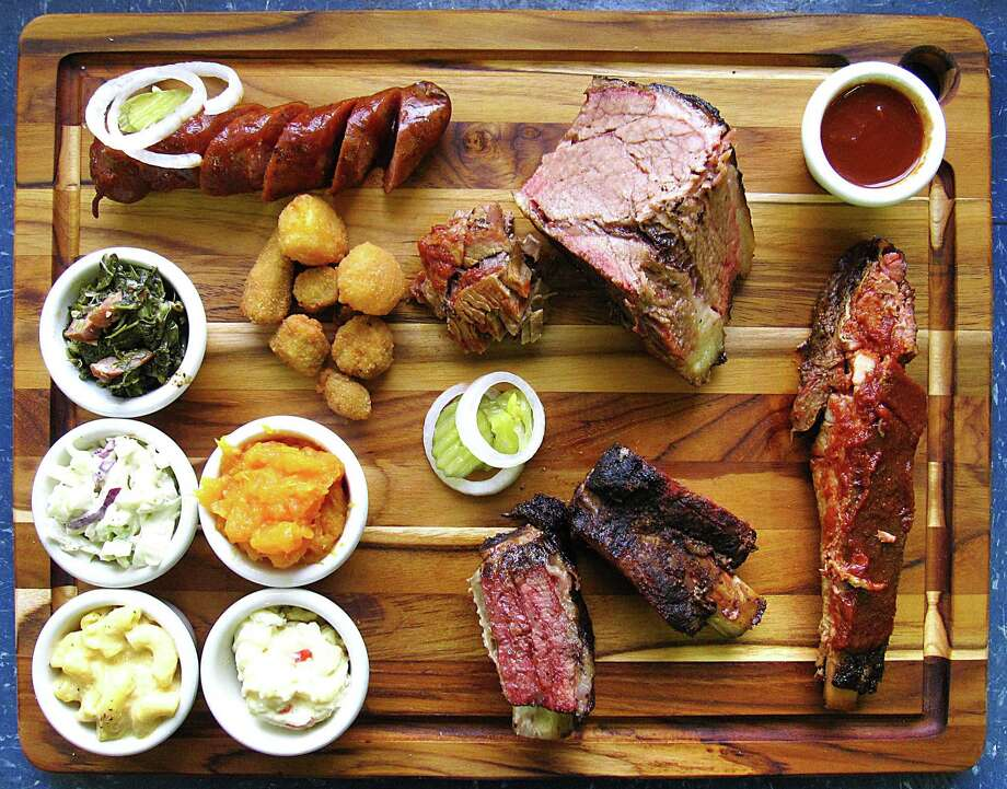Meat and sides from The Rib House. Clockwise from top left: sausage, brisket, barbecue sauce, pork spare rib, beef short ribs, potato salad, mac and cheese, cole slaw, collard greens, fried okra, corn nuggets and yams. Photo: Mike Sutter /San Antonio Express-News