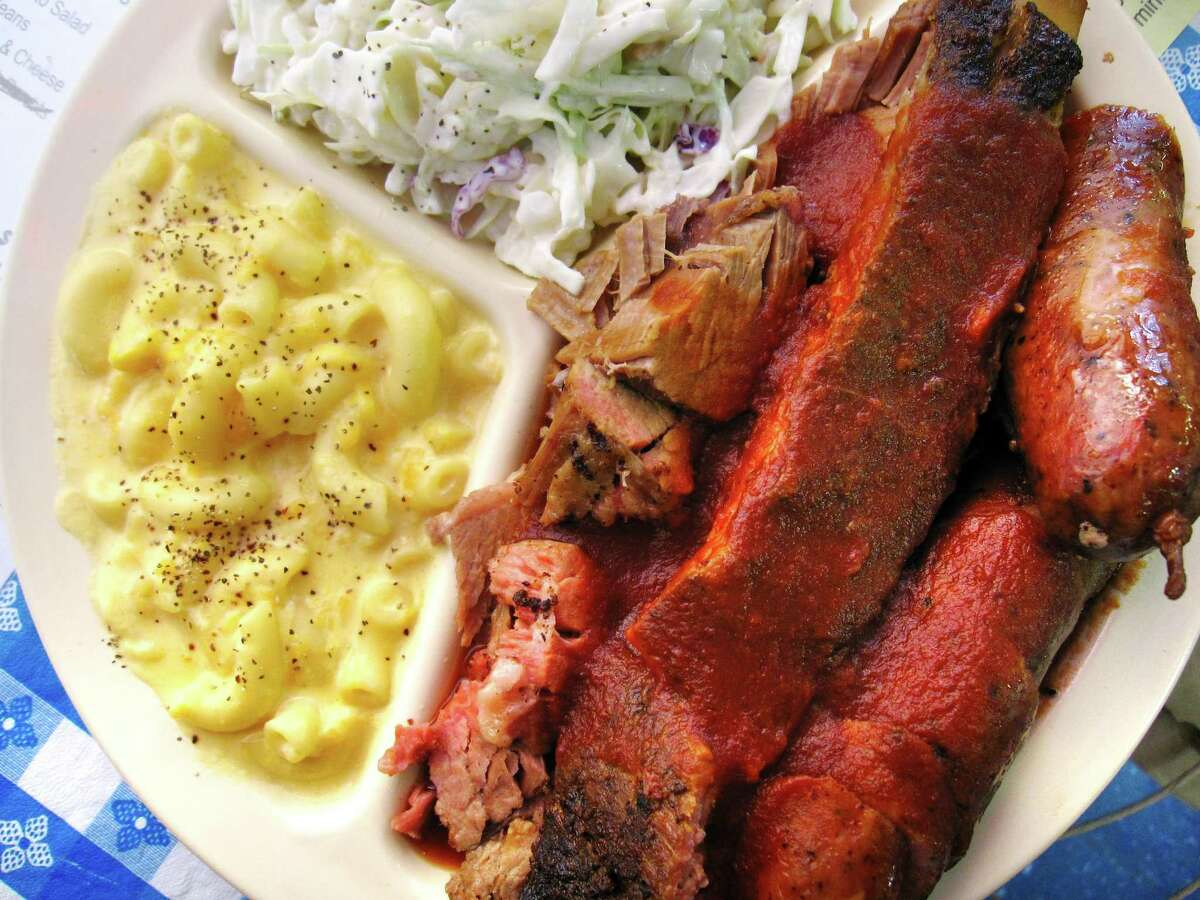 A three-meat plate with a pork rib, brisket, sausage, mac and cheese and cole slaw from The Rib House.