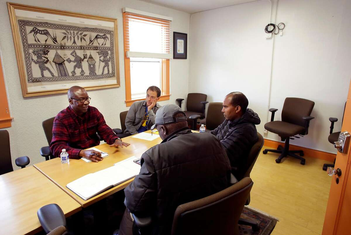 (l to r) Director, Adoubou Traore, meets with staff members, Joe Sciarrillo, Charles Jackson and Yohannes Yetbarek at the offices of the African Advocacy Network offices in San Francisco, Calif., on Thurs. Feb. 22, 2018.