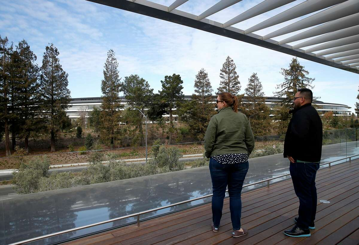 Guests take in the view of the circular Apple headquarters building from the Apple Park Visitor Center located across the street in Cupertino, Calif. on Tuesday, Feb. 20, 2018.