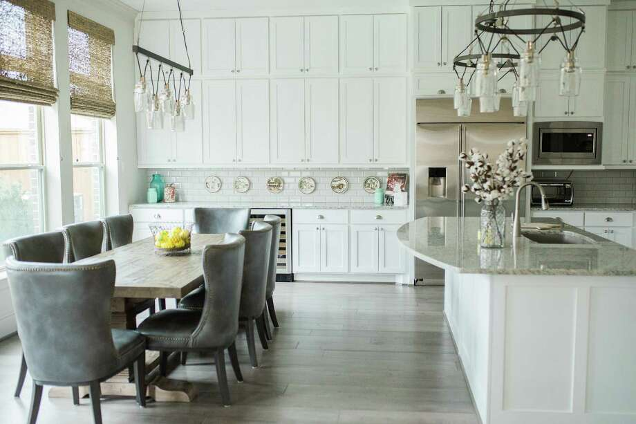 Holly and Tom Forney's townhome kitchen features tall cabinets and unique metal cable, hand-blown mercury glass chandeliers that immediately catch the eye. Photo: Ashlie Simon