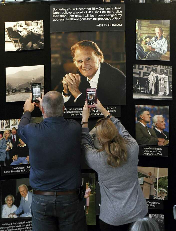 Chuck and Angela Riddle, of Morganton, N.C., photograph a memorial display in tribute to Rev. Billy Graham inside the chapel at the Billy Graham Training Center at the Cove on Wednesday in Asheville, N.C. The couple came to pay their respects and said Graham was a big influence in their lives. Photo: Kathy Kmonicek /Associated Press / FR170189 AP