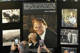 Chuck and Angela Riddle, of Morganton, N.C., photograph a memorial display in tribute to Rev. Billy Graham inside the chapel at the Billy Graham Training Center at the Cove on Wednesday in Asheville, N.C. The couple came to pay their respects and said Graham was a big influence in their lives.
