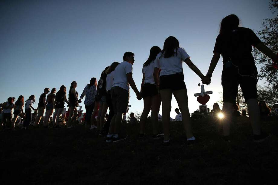 Students and family members holds hands around a makeshift memorial in front of Marjory Stoneman Douglas High School. in Parkland, Fla., where 17 people were killed on Feb. 14. A reader says blaming the tragedy on guns is a non-starter in the national debate about how to prevent future attacks. Photo: Mark Wilson / / 2018 Getty Images