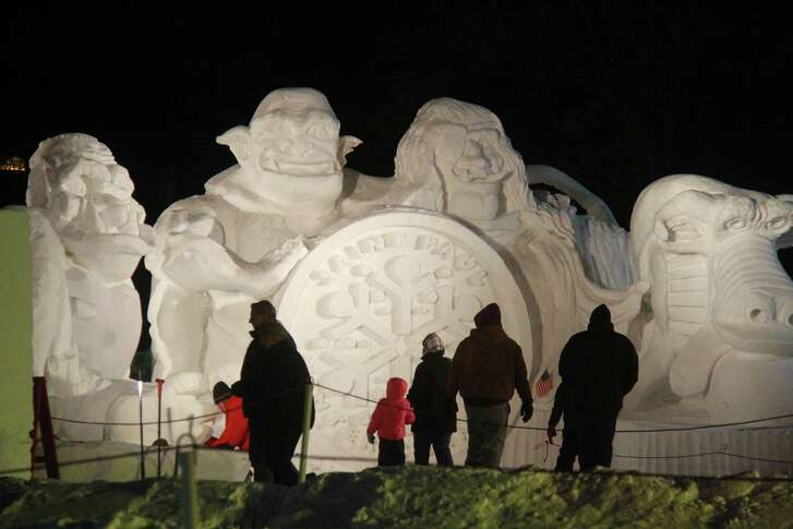 Tourists check out the Vulcans Snow Park at night, part of the Saint Paul Winter Carnival in St. Paul, Minn. These people seem to be having fun, but for others, the frigid temperatures make the indoors more inviting.