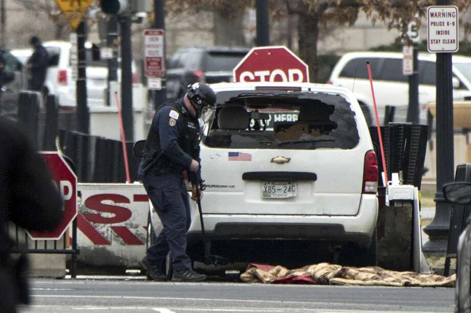 A Secret Service officer checks a white passenger vehicle that struck a security barrier that guards the southwest entrance to the White House grounds off of 17th Street n Washington, Friday, Feb. 23, 2018. (AP Photo/J. Scott Applewhite) Photo: J. Scott Applewhite/AP