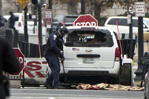 A Secret Service officer checks a white passenger vehicle that struck a security barrier that guards the southwest entrance to the White House grounds off of 17th Street n Washington, Friday, Feb. 23, 2018. (AP Photo/J. Scott Applewhite)