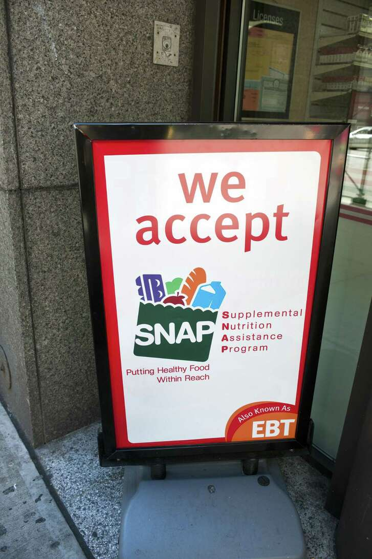 """A sign in front of a 7-Eleven in New York announces that the convenience store accepts SNAP (Supplemental Nutrition Assistance Program), on October 20, 2012. President Donald Trump has called for replacing half of the food stamp benefits received with a food delivery service tentatively called """"America's Harvest Box."""""""