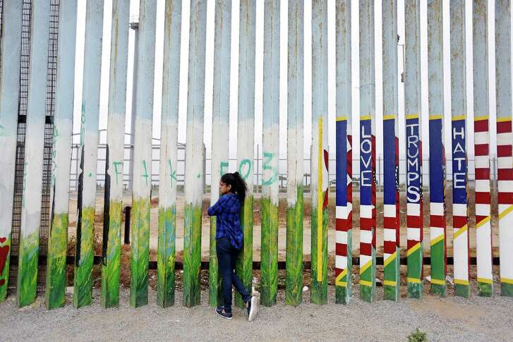 Jade Vega, 14, of Peru, peers through the fence at Friendship Park at the beach along the U.S.-Mexico border in Tijuana, Baja Calif., on July 29, 2017. Vega, who says she is a U.S. citizen, was visiting her mother in Tijuana for the summer.