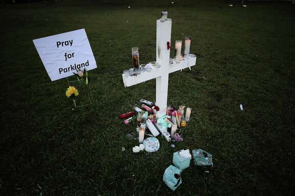 Candles glow after a late-night vigil for victims of the mass shooting at Marjory Stoneman Douglas High School in Parkland, Fla. In the wake of the murders, a reader notes a disturbing lack of urgency on gun control.