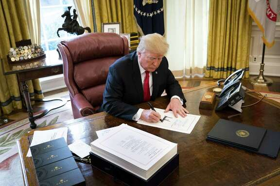 President Donald Trump signs the tax reform bill in the Oval Office of the White House in Washington, Dec. 22. Support for the law is growing even among Democrats, buoying Republican hopes for this years congressional elections.