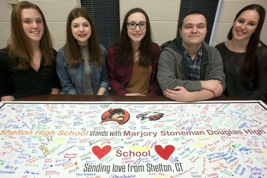 Shelton High School students, from left, Julia Jacob, Megan Bisson, Stephanie Johnson, Noah Swatt and Tiana Boccuzzi, sit with a banner signed by hundreds of students in Shelton on Friday. The banner will be sent as a gesture of solidarity to the students of Marjory Stoneman Douglas High School, in Parkland, Fla., the scene of a shooting on Feb. 14. Photo: Ned Gerard / Hearst Connecticut Media / Connecticut Post