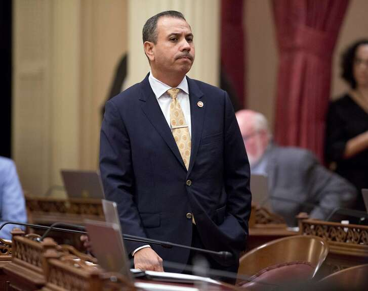 """FILE - In this Jan. 3, 2018 file photo, state Sen. Tony Mendoza, D-Artesia, stands at his desk after announcing that he will take a month-long leave of absence while an investigation into sexual misconduct allegations against him are completed, during the opening day of the Senate in Sacramento, Calif. Mendoza announced Thursday, Feb. 22, 2018 that he is resigning over sexual misconduct allegations just ahead of a possible vote by his colleagues to expel him. In his resignation letter, Mendoza called the Senate's process """"farcical"""" and unfair and is still considering running for re-election in the fall. (AP Photo/Steve Yeater, File)"""