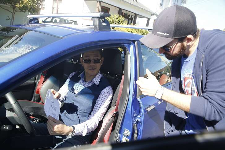 Tyler Karon (right) gives a thumbs up as David Chu (left) shows him the car insurance as Karon picks up Chu's car which he rented through Turo in Alameda, Calif., on Friday, February 23, 2018.