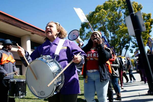 Marta Dominguez bangs on a drum as healthcare workers, concerned about job cuts and outsourcing, stage a rally outside of the Kaiser Permanente Medical Center in San Jose, Calif. on Friday, Feb. 23, 2018.
