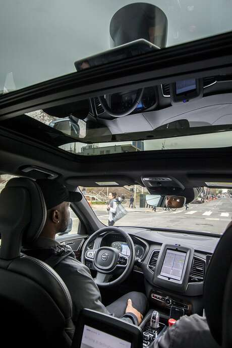 From left: Uber's Devin Greene demonstrates the self-driving Volvo XC90 SUV on Tuesday, Dec. 13, 2016 in San Francisco, Calif. LIDAR, a laser system that maps out the car's surroundings, is seen on top of the roof.