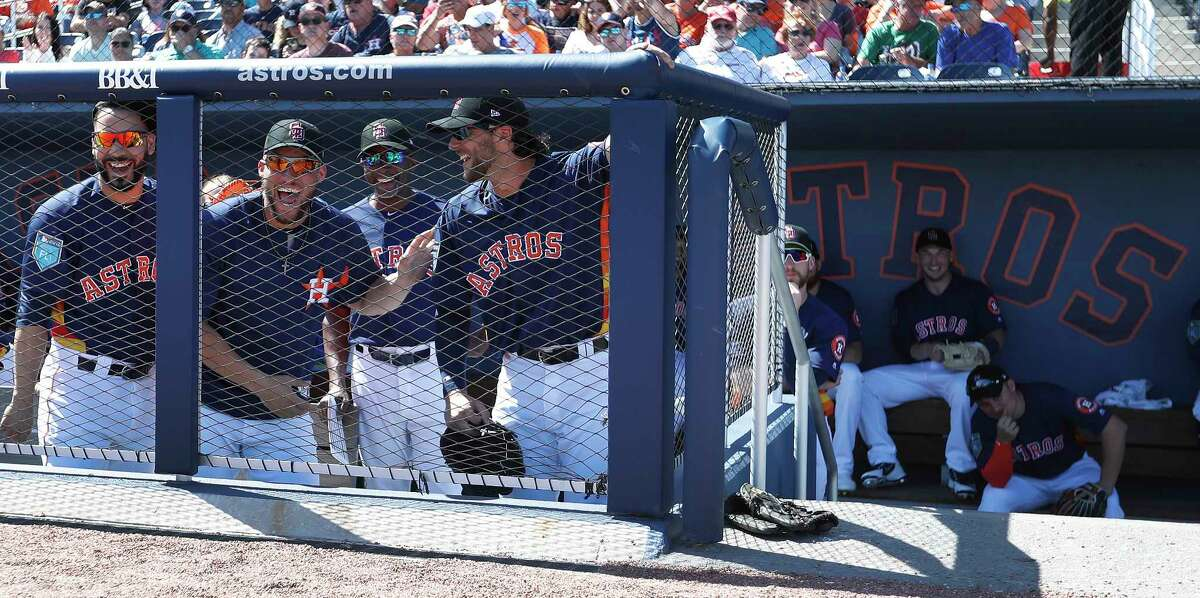 Houston Astros Marwin Gonzalez, George Springer and Jake Marisnick wearing Stoneman Douglas Eagles baseball caps in the dugout before the start of the Houston Astros spring training game against the Nationals at The Fitteam Ballpark of the Palm Beaches, Friday, Feb. 23, 2018, in West Palm Beach.