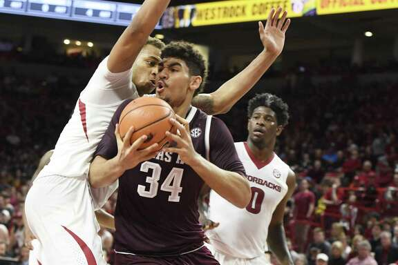 Texas A&M center Tyler Davis tries to drive past Arkansas defender Daniel Gafford during the second half of an NCAA college basketball game Saturday, Feb. 17, 2018, in Fayetteville, Ark. (AP Photo/Michael Woods)
