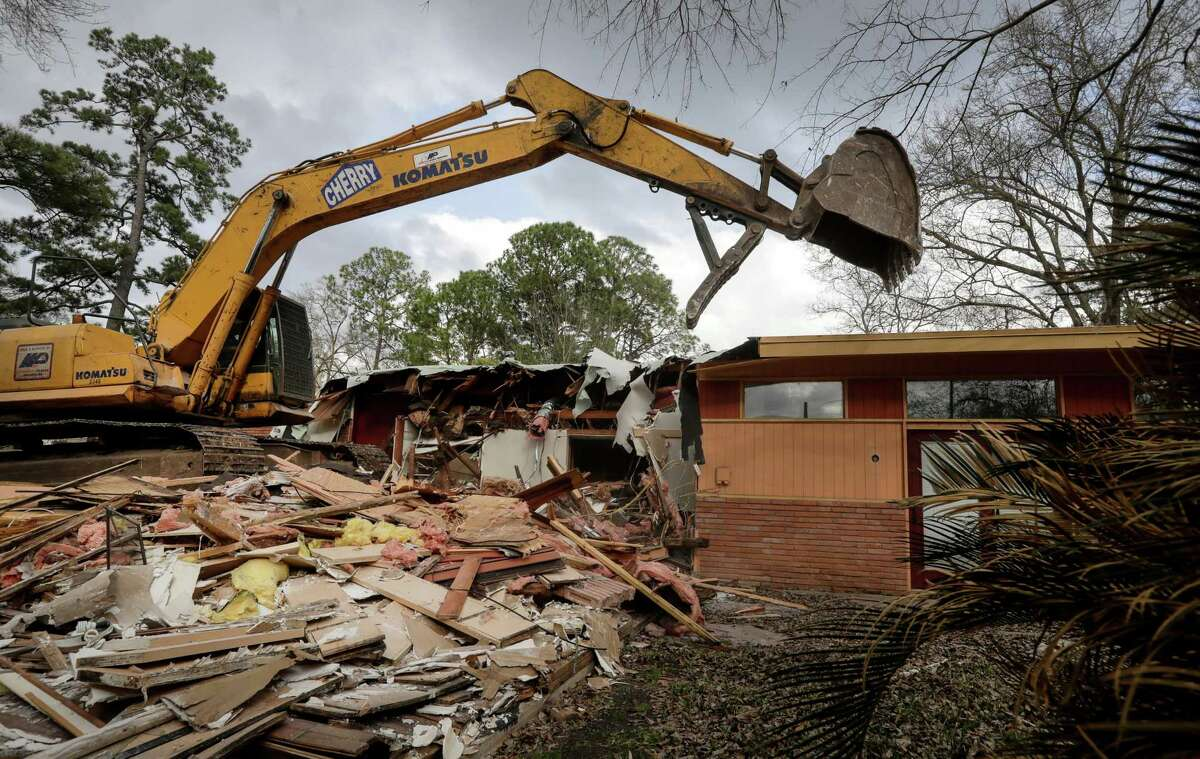 A home flooded during Hurricane Harvey is demolished, Feb. 16, 2018, in Houston. Texas insurance companies say they've had a spike in flood insurance policies after the storm's destruction. ( Jon Shapley / Houston Chronicle )