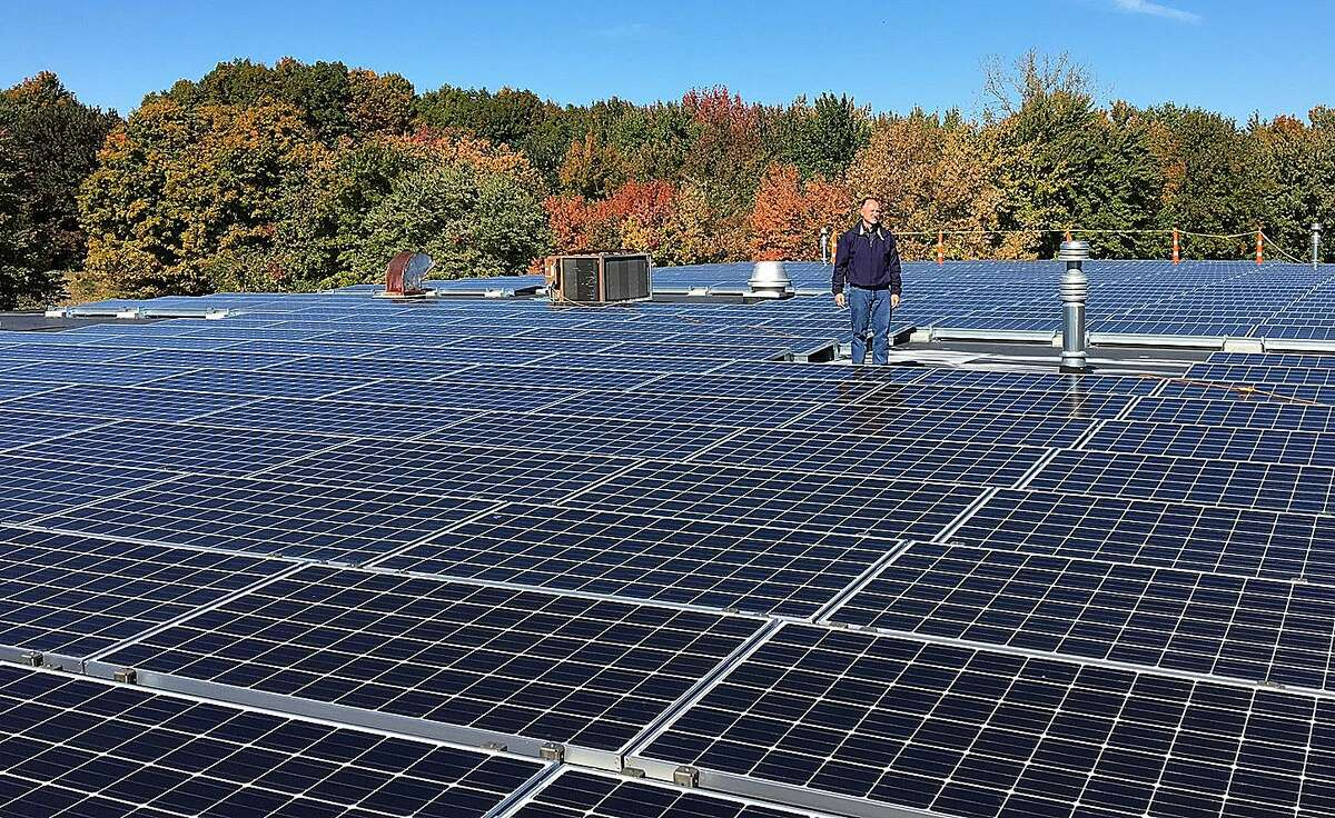 Joe Young, partner with Tier ONE Machining and Assembly, stands on the roof of his business in Newtown, Conn., surrounded by 810 solar panels, which have recently been installed.