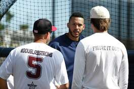Houston Astros shortstop Carlos Correa chats with Douglas Stoneman High School's baseball head coach Todd Fitz-Gerald, left, and his son, Hunter Fitz-Gerald, right, during baseball spring training in West Palm Beach, Fla., Friday, Feb. 23, 2018. (Karen Warren/Houston Chronicle via AP)