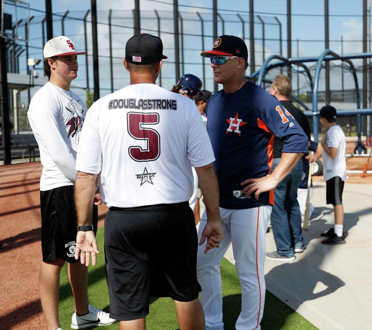 Houston Astros manager A.J. Hinch talks with Douglas Stoneman High School's baseball head coach Todd Fitz-Gerald, center, and his son, Hunter Fitz-Gerald, left, during baseball spring training in West Palm Beach, Fla., Friday, Feb. 23, 2018. (Karen Warren/Houston Chronicle via AP)