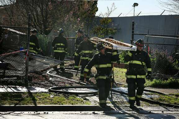 Firefighters carry a ladder from the scene where a fire broke out in a building at 1449 Miller Avenue on Friday, February 23, 2018 in Oakland, Calif. The cause is under investigation.
