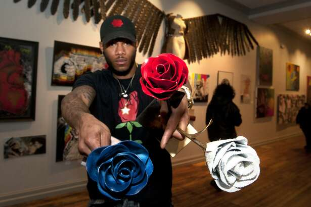 """Artist and sculptor Byron Troy holds a few of his welded steel roses during the opening reception for the CT Arts Against Violence art show at the Blends Gallery, in Bridgeport, Conn. Feb. 23, 2018. This year's show is, featuring a wide variety of art from local artists is titled """"Less Guns, More Roses""""."""