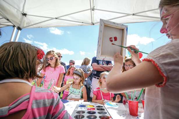 Children make their own canvas paintings during the Arts in the Park event on Saturday, March 14, 2015, at Rob Fleming Park.