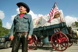 Welocome Wilson, left, stands by the Desparados wagon after arriving to Memorial Park with the Salt Grass Trail Riders on Friday, Feb. 23, 2018, in Houston.