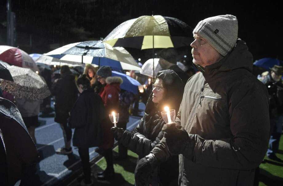 Gary McEvoy, right, and Joyce Murty, both from Newtown, listen as the names of victims of mass shootings in the United States are read aloud at the Junior Newtown Action Alliance community vigil to remember the victims from Marjory Stoneman Douglas High School shooting in Parkland, Florida. Friday night, February 23, 2018, at Newtown High School, in Newtown, Conn. Photo: H John Voorhees III / Hearst Connecticut Media / The News-Times