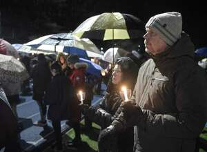 Gary McEvoy, right, and Joyce Murty, both from Newtown, listen as the names of victims of mass shootings in the United States are read aloud at the Junior Newtown Action Alliance community vigil to remember the victims from Marjory Stoneman Douglas High School shooting in Parkland, Florida. Friday night, February 23, 2018, at Newtown High School, in Newtown, Conn.