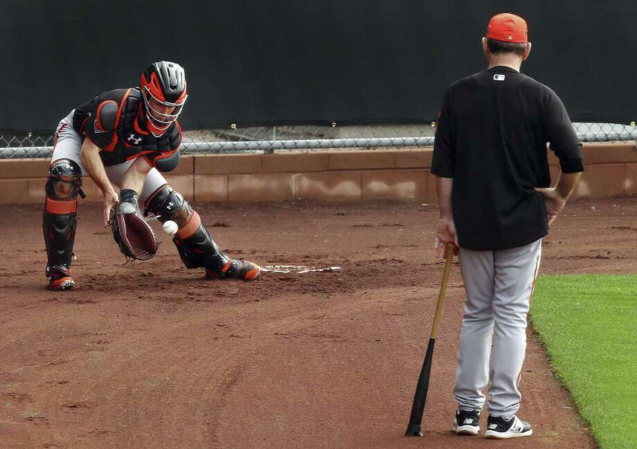 San Francisco Giants manager Bruce Bochy, right, watches catcher Buster Posey during a spring training baseball practice in Scottsdale, Ariz.  Photo: Ben Margot / Associated Press / Copyright 2018 The Associated Press. All rights reserved.
