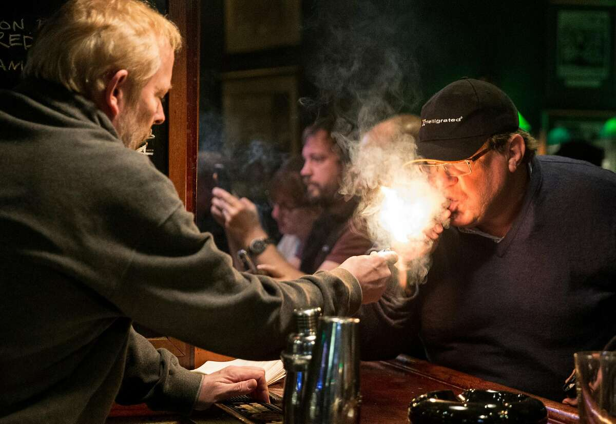 Founding partner Curtis Post lights a cigar for Chris Cole of Naples, Florida at Occidental Cigar Club Thursday, Feb. 22, 2018 in San Francisco, Calif.