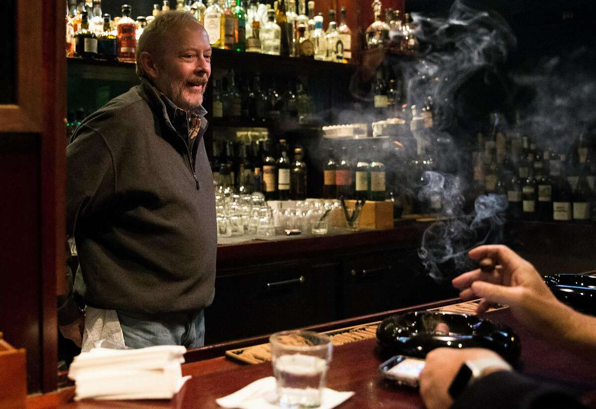 Founding partner Curtis Post laughs while chatting with patrons behind the bar of Occidental Cigar Club Thursday, Feb. 22, 2018 in San Francisco, Calif.
