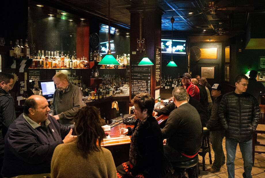 Patrons enjoy drinks and cigars at the Occidental Cigar Club in San Francisco. Photo: Jessica Christian, The Chronicle