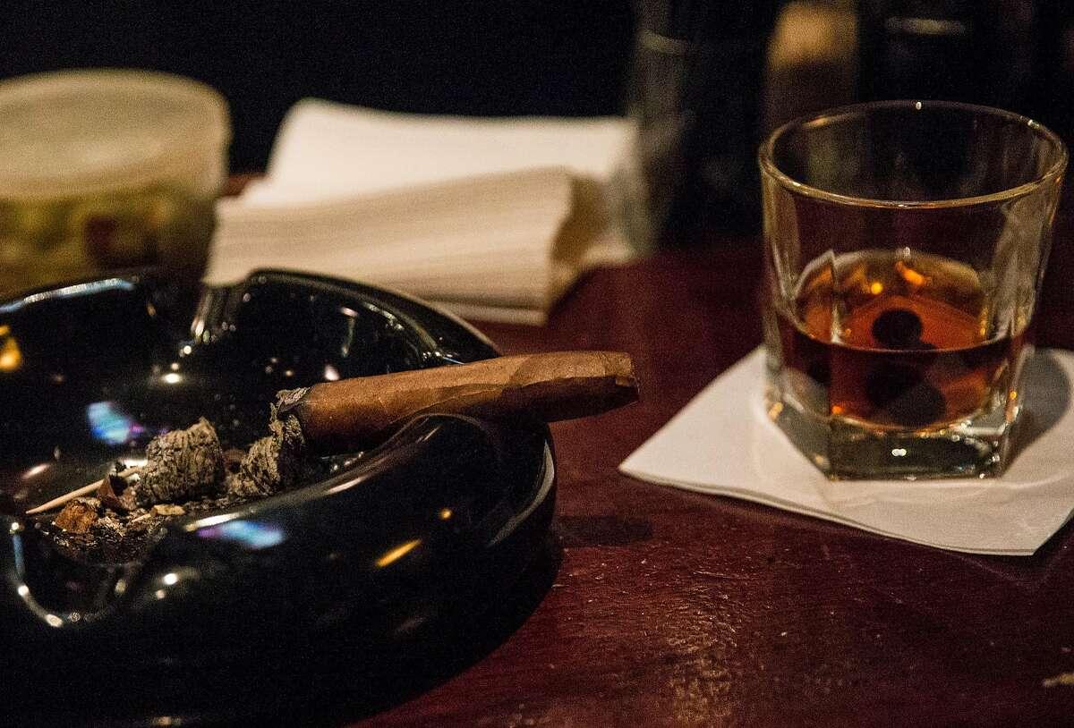 A lit cigar sits in an ashtray near an Old Fashioned drink at Occidental Cigar Club Thursday, Feb. 22, 2018 in San Francisco, Calif.