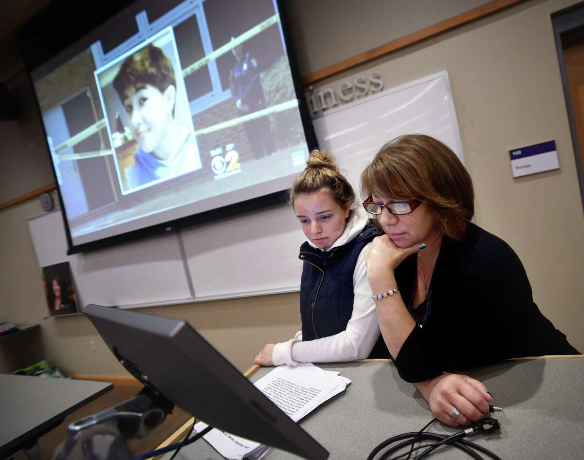 Alia Mostafa, left, president of the Collegiate Health Service Corps at the University of Bridgeport and a childhood friend of Maren Sanchez, and Sanchez's mother, Donna Cimarelli, watch a video segment reporting on Sanchez's death during a talk at the University of Bridgeport Friday.