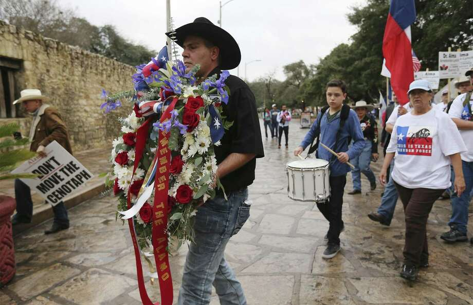 This Is Texas Freedom Force's Brandon Burkhardt carries a wreath to place at the front of the Alamo as the group hosts a Remember The Alamo remembrance rally Friday. A crowd of supporters for keeping the Cenotaph in place and who disagree with proposed changes to the grounds of the Alamo were joined by Alamo descendants and politicians running against Land Commissioner George P. Bush for a procession around the Alamo, a wreath-laying in front of the Shrine of Texas and then a rally. Photo: Kin Man Hui /San Antonio Express-News / ©2018 San Antonio Express-News