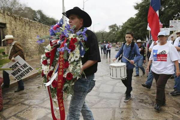 This Is Texas Freedom Force's Brandon Burkhardt carries a wreath to place at the front of the Alamo as the group hosts a Remember The Alamo remembrance rally Friday. A crowd of supporters for keeping the Cenotaph in place and who disagree with proposed changes to the grounds of the Alamo were joined by Alamo descendants and politicians running against Land Commissioner George P. Bush for a procession around the Alamo, a wreath-laying in front of the Shrine of Texas and then a rally.